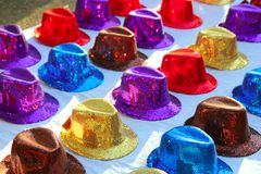 Colorful sequins hats in rows in outdoor market. Over white Royalty Free Stock Images
