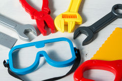 Colorful set of plastic toy tools for children on a wooden background Royalty Free Stock Images