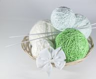 Colorful set of yarn ball green and white in a basket. On knitted white  snowflake, white background with space for text royalty free stock image