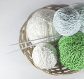 Colorful set of yarn ball green and white in a basket. On knitted white  snowflake, white background with space for text stock image