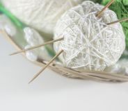 Colorful set of yarn ball green and white in a basket. On knitted white  snowflake, white background with space for text stock images
