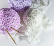 Colorful set of yarn ball pink and purple. With knitting needles on knitted white  snowflake, white background with space for text stock photography