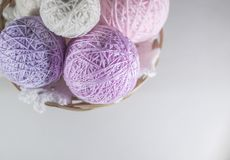 Colorful set of yarn ball pink, violet and purple in a basket. On knitted white  snowflake, white background with space for text royalty free stock image