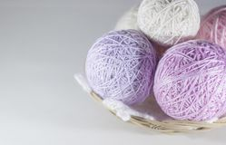 Colorful set of yarn ball pink, violet and purple in a basket. On knitted white  snowflake, white background with space for text stock photography