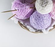 Colorful set of yarn ball pink, violet and purple in a basket. On knitted white  snowflake, white background with space for text stock images