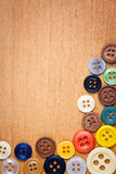 Colorful sewing buttons on a wooden background Stock Image