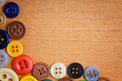 Colorful sewing buttons on a wooden background Royalty Free Stock Image
