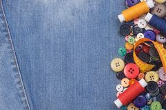 Colorful sewing buttons, yellow measuring tape and thread spools stock photography