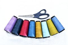 Colorful sewing thread reels on white background with scissors.  stock photography