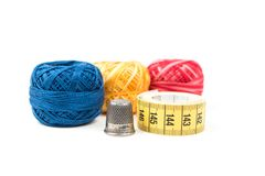 Colorful sewing threads with metal thimble and yellow measuring tape Stock Photography