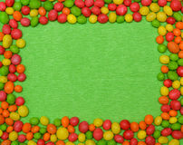 Colorful shaped candies on green textured paper. The frame of candies with space for text or festive design. Color - green, red, yellow, orange Royalty Free Stock Photo