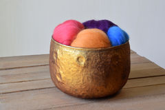 Colorful sheep wool fiber in a copper glass bowl on a wood mat. Copper glass bowl of colorful sheep wool fiber in blue, pink, purple, and orange. The bowl is on stock image