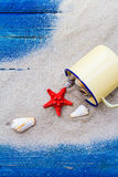 Colorful shells cup sand strewn blue boards Stock Images