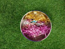Colorful shiny wire in round aluminum bin on green yard Stock Images