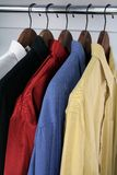 Colorful shirts on wooden hangers. Shirts of different colors on wooden hangers royalty free stock images
