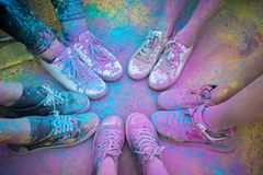 The colorful shoes and legs of teenagers at color run event.  royalty free stock photo