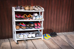 Colorful Shoes on a Plastic Shoe Rack, Outside a House. A variety of colorful shoes, neatly ordered on a plastic shoe rack outside a wooden house stock photos