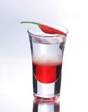 Colorful shooter with reflection. Colorful layered shot with reflection. Alcohol red shooter with chili pepper Royalty Free Stock Photo