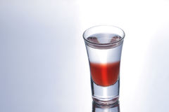 Colorful shooter with reflection. Colorful layered shot isolated on white gray gradient background with reflection. Alcohol shooter Stock Photos