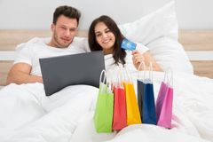 Colorful shopping bags with couple lying on bed Stock Photo
