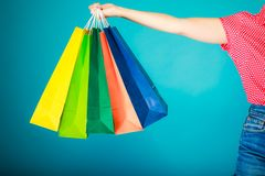Colorful shopping bags in female hand. Sale retail. Closeup of colorful paper shopping bags in female hand on vibrant blue. Woman girl buying clothes. Sale and royalty free stock photos
