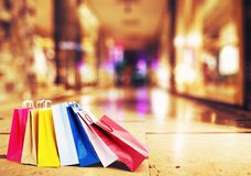 Colorful shopping bags on the ground with a gallery of luxurious shops in the background. Concept of sales and shopping in stores stock images