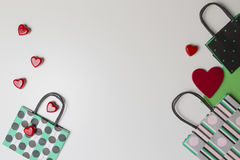 Colorful shopping bags and red hearts on white background. Top view. Copy space for text Stock Photo