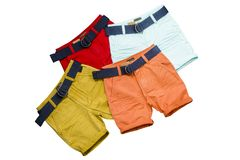 Colorful shorts whith belts laying on each other. Four pairs of colorful shorts whith belts laying on each other royalty free stock images