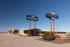 Colorful sign of the Sunset Motel with Whiting Bros. filling station in background. royalty free stock images