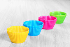 Colorful silicone baking cups. On wooden background Royalty Free Stock Photo