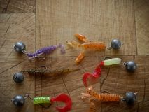 Silicone colorful fishing baits with plummets on wooden table. Toned image and top view royalty free stock photography