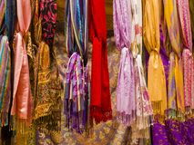 Colorful silk scarvers hanging on market stall, India. Row of colorful silk scarvers hanging on market stall, India Stock Photo