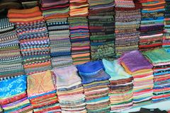 Colorful silk and woven fabric for sale in a Cambodian market. Colorful handwoven silk and other patterned fabric for sale in a market in Battambang, Cambodia Royalty Free Stock Image