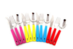 Colorful silverware. Colorful forks knifes and spoons with white background Royalty Free Stock Photos
