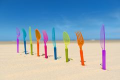 Silverware at the beach. Colorful silverware standing in sand at the beach Stock Photo
