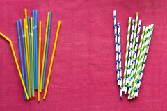 Colorful single use disposable plastic straws vs paper straws stock image
