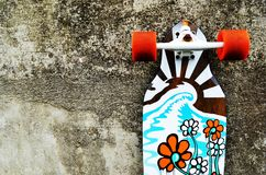 Skateboard leaning against a stone wall royalty free stock images