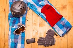 Colorful ski glasses, gloves and helmet. On wooden table. Winter ski theme royalty free stock photography