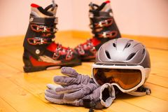 Colorful ski glasses, gloves and helmet. On wooden table. Winter ski theme stock photography