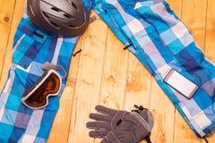 Colorful ski glasses, gloves and helmet. On wooden table. Winter ski theme stock image