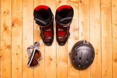 Colorful ski glasses, gloves and helmet. On wooden table. Winter ski theme stock images