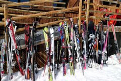 Colorful ski and snowboards resting against wooden ski restaurant Royalty Free Stock Photography
