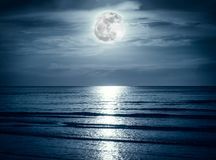 Colorful sky with dark cloud and bright full moon over seascape. Royalty Free Stock Photography