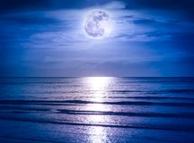 Colorful sky with dark cloud and bright full moon over seascape. Landscape of blue sky with dark cloudy and bright full moon over seascape in the evening Stock Photography