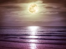 Colorful sky with dark cloud and bright full moon over seascape. Royalty Free Stock Image