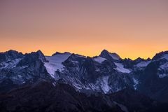 Colorful sky at dusk beyond the glaciers on the majestic peaks of the Massif des Ecrins 4101 m, France. Telephoto view from dist Royalty Free Stock Photography