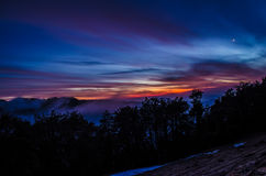 Colorful sky during dusk in mountiains. A view of colorful sky with clouds over mountains at dusk Royalty Free Stock Images