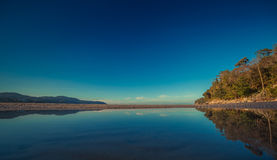 Colorful sky and the ocean smooth reflection in morning time before sunrise. Ocean simple beach panorama. Thailand Stock Photos