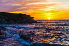 Colorful sky over Porto Ferro rocky shore at sunset Royalty Free Stock Photo