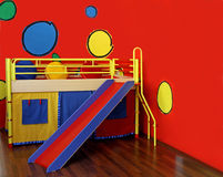 Colorful sledge. Colorful bed in childs room with red wall and sledge Stock Images